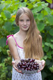 Beautiful girl holding a bowl of cherries in the garden Royalty Free Stock Image