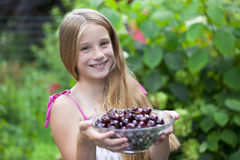 Beautiful girl holding a bowl of cherries in the garden Stock Photo