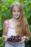 Beautiful girl holding a bowl of cherries in the garden Royalty Free Stock Photo