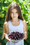 Beautiful girl holding a bowl of cherries in the garden Stock Image