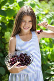 Beautiful girl holding a bowl of cherries in the garden Stock Photos
