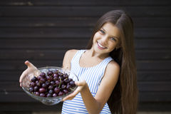 Beautiful girl holding a bowl of cherries in the garden Royalty Free Stock Photography