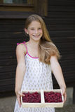 Beautiful girl holding a box with a raspberry Stock Photos