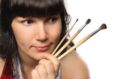 Beautiful girl holding brushes. Stock Photo