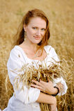 Beautiful girl holding a bunch of wheat ears Royalty Free Stock Photo