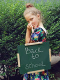 Beautiful girl  holding Chalkboard with words Back to School. Outdoor photo. Education and kids fashion concept Stock Photos