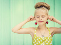 Beautiful girl holding cherries as earrings -style Rockabilly. Stock Photos