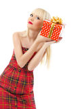 Beautiful girl holding christmas gift in red dress Royalty Free Stock Image