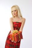 Beautiful girl holding christmas gift in red dress Royalty Free Stock Photography