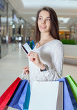 Beautiful girl holding a credit card in a shopping centre royalty free stock image