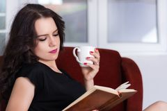 Beautiful girl holding cup of coffee and reading book at home royalty free stock photography