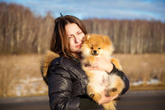Beautiful girl holding a dog Spitz. Small breeds. Photographing outdoors Royalty Free Stock Photos