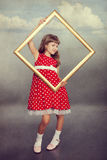 Beautiful girl holding an empty frame Stock Image