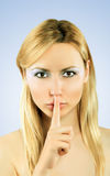 Beautiful girl holding finger on lips Royalty Free Stock Photography