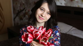 Beautiful girl holding flowers, looking at the camera, smiling, flirting. Beautiful girl with green eyes with tulips in hands  looking at the camera, smiling stock video footage