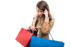Beautiful girl holding gift bags while doing shopping. For fall season isolated on white Stock Photography
