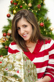 Beautiful girl holding gift Christmas tree background Royalty Free Stock Photography