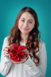 Beautiful girl holding a gift in the form of heart with a red bo Stock Images