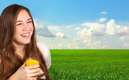 beautiful girl holding a glass of juice and smiling on the background of the field royalty free stock images