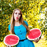 Beautiful girl holding halves of watermelon and shows tongue Stock Photography