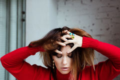 Beautiful girl is holding hands behind her head. Beautiful girl in a red sweater and rings is holding her hands behind her head, frantic, bewildered, not stock photos