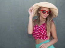 Beautiful girl holding hat by one hand Royalty Free Stock Image