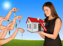 Beautiful girl holding house with label. Many Stock Photography