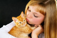Beautiful girl holding a kitten on the hands stock photo