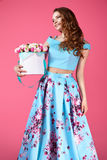 Beautiful girl holding large bouquet of paper flowers in box. Young pretty girl standing and holding white box with paper flowers. Vogue fashion style studio Royalty Free Stock Photos