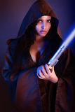 Beautiful girl holding a lightsaber. On a gray background Stock Image