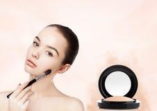 Beautiful girl holding makeup brush for foundation Royalty Free Stock Photos
