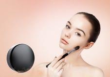 Beautiful girl holding makeup brush for foundation Stock Image