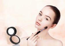 Beautiful girl holding makeup brush for foundation Royalty Free Stock Image
