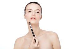 Beautiful girl holding makeup brush for foundation Stock Photos