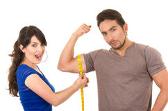 Beautiful girl holding measuing tape around. Beautiful surprised girl holding measuing tape around handsome muscular man's arm biceps isolated on white Royalty Free Stock Photos