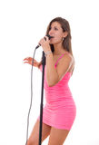 Beautiful girl holding microphone and singing in a dress Royalty Free Stock Images