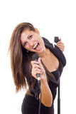 Beautiful girl holding microphone and singing loud in black dres Stock Photography
