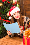 Beautiful girl holding New Year and Christmas congratulation. Beautiful girl sitting at the wooden table and reading New Year and Christmas congratulation. Happy Royalty Free Stock Photography