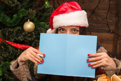 Beautiful girl holding a New Year and Christmas post card. New Year and Christmas concepts. Beautiful girl holding a New Year and Christmas post card and hiding Stock Images