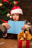 Beautiful girl holding a New Year and Christmas post card. New Year and Christmas concepts. Serious beautiful girl in Santa hat holding a New Year and Christmas Stock Photos