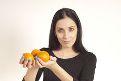Beautiful girl holding oranges in hands. Beautiful girl in a studio posing to photographer Royalty Free Stock Photos