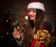 Beautiful girl holding a present near New Year tree Stock Images