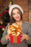 Beautiful girl holding a present near New Year tree Royalty Free Stock Photography