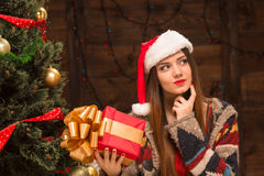 Beautiful girl holding a present near New Year tree Stock Photography