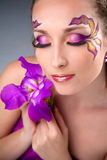 Beautiful girl  holding purple iris. Beautiful girl with bright make-up holding purple iris Royalty Free Stock Photo
