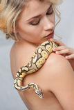 Beautiful girl  holding a python, which wraps Royalty Free Stock Image