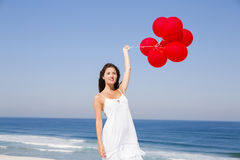 Beautiful girl holding red ballons Stock Images