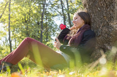 Beautiful girl holding red heart on a stick while sitting on the Stock Images