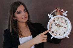 Beautiful girl holding retro clock . studio. Girl in a black business suit and white shirt Royalty Free Stock Photography