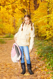 Beautiful girl holding rucksack standing in forest Royalty Free Stock Images